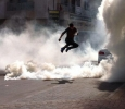 Bahrain, protester leaping through tear gas